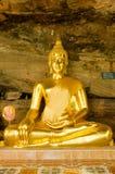 Estatua de oro de Buda en cueva Foto de archivo libre de regalías