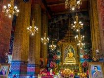 Estatua de oro de Buda en el trono y en templo con las columnas grandes Foto de archivo libre de regalías
