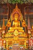Estatua de oro de buddha dentro de un templo Fotos de archivo