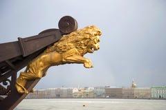 Estatua de oro de un león en la nariz de la nave vieja en el fondo de la tarde nublada de marzo del terraplén del palacio Imagenes de archivo