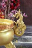 Estatua de oro del caballo del dragón al lado de la hornilla de incienso del oro Foto de archivo