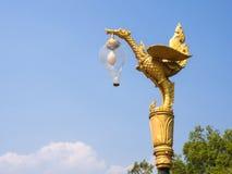 Estatua de oro del cisne con la lámpara de calle en el cielo azul Imágenes de archivo libres de regalías