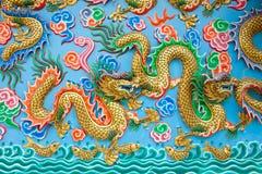 Estatua de oro del dragón en la pared azul Fotos de archivo