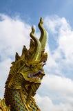 Estatua de oro del Naga con el cielo azul Imagen de archivo libre de regalías