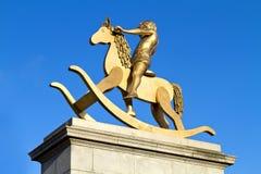 Estatua de oro del niño joven en caballo de oscilación fotos de archivo libres de regalías