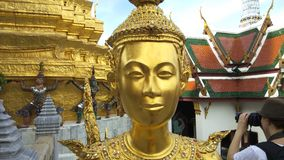 Estatua de oro de Kinnari en el templo de Emerald Buddha Wat Phra Kaew en Royal Palace magnífico, Bangkok Tailandia almacen de metraje de vídeo