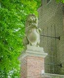 Estatua de piedra del león en un polo del ladrillo imágenes de archivo libres de regalías
