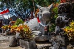 Estatua de piedra de la vaca grande con una guirnalda en colores rojos y blancos y bandera indonesia para el Día de la Independen fotos de archivo