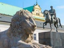 Estatua de piedra de un león y de un monumento a príncipe Jozef Poniatowski cerca del palacio presidencial, Varsovia Foto de archivo