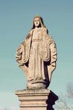 Estatua de piedra vieja de la Virgen en la piedra sepulcral en el cementerio Imágenes de archivo libres de regalías