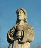 Estatua de piedra vieja de una mujer con una taza para la comunión santa en Fotografía de archivo libre de regalías