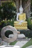 estatua de plata de Buda con el traje de oro en jardín Imagenes de archivo