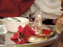 Estatua de plata de señor Ganesha rodeada por los pétalos color de rosa rojos para el rezo Imagen de archivo libre de regalías