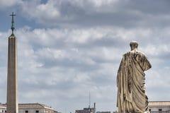 Estatua de San Pedro fuera de la basílica de San Pedro en la Ciudad del Vaticano con el obelisco del Vaticano en fondo fotografía de archivo