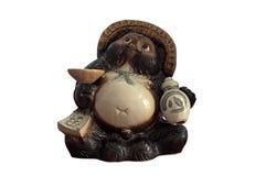 Estatua de Tanuki con la botella del motivo en el fondo blanco foto de archivo libre de regalías
