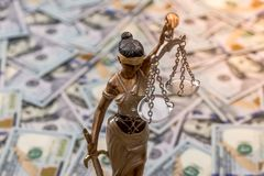 Estatua de Themis que se coloca contra la perspectiva de dólares Fotos de archivo libres de regalías