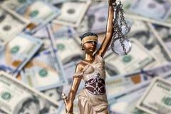 Estatua de Themis que se coloca contra la perspectiva de dólares Imagen de archivo