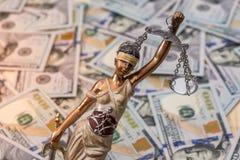 Estatua de Themis que se opone al fondo de dólares Fotos de archivo libres de regalías