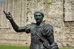 Estatua de Trajan delante de una sección de la pared romana, torre Imágenes de archivo libres de regalías