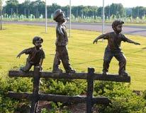 Estatua de tres Young Boys que juega en una cerca de madera Foto de archivo