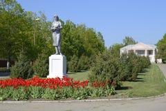 Estatua de un granjero colectivo en un pedestal La herencia de la era soviética Una cama de flor con los tulipanes y los árboles  Foto de archivo libre de regalías