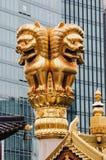 Estatua de un león de oro en el tejado de un templo budista contra el contexto de un edificio moderno Imagen de archivo libre de regalías