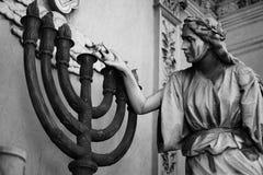 Estatua de una mujer que enciende el centro de una lámpara de siete velas foto de archivo