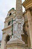 Estatua del ángel con la cruz delante de Karlskirche Foto de archivo libre de regalías