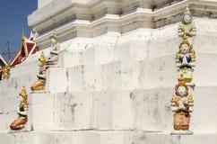 Estatua del ángel en el edificio y el chedi de Wat Wachirathammasatit Foto de archivo libre de regalías