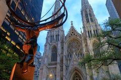 Estatua del atlas y la catedral de St Patrick en la noche situada en Fifth Avenue, Manhattan, NYC Foto de archivo libre de regalías