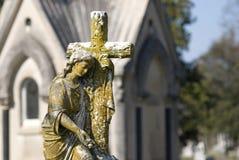 Estatua del cementerio de la mujer con la cruz imagenes de archivo