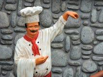 Estatua del cocinero cerca de la pared de piedras Fotos de archivo