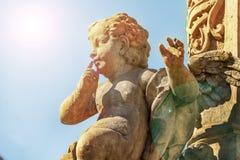 Estatua del cupido hecha de la piedra, un monumento del amor, resplandor del sol, el apuntar gordo divertido del cupido imagen de archivo libre de regalías