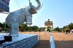 Estatua del elefante fuera de las tazas y de las placas al lado de la señal de Patuxai Victory Monument The One Attractive de la  fotos de archivo