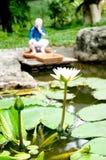Estatua del loto y de la muñeca en la piscina Fotografía de archivo