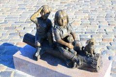 Estatua del muchacho y de la muchacha cerca del pequeño perrito Imagenes de archivo