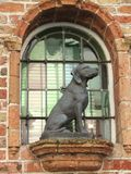 Estatua del perro delante del vitral Fotos de archivo