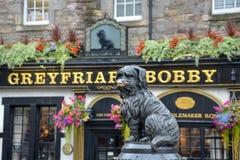 Estatua del perro Greyfriars Bobby delante del pub en Edinbu foto de archivo