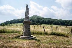 Estatua del SV Antonin Paduansky cerca del pueblo de Kocourov en Ceske Stredohori con la huerta y la colina jovenes en el fondo Fotografía de archivo