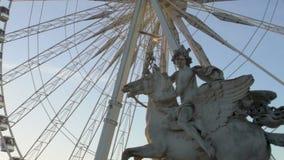 Estatua ecuestre de Pegaso delante de la rueda grande en la puesta del sol, haciendo turismo en París almacen de metraje de vídeo