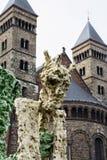 Estatua extraña amarilla con la iglesia europea vieja como fondo Imágenes de archivo libres de regalías