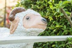 Estatua linda de las ovejas blancas del primer para la decoración en el fondo del jardín Fotos de archivo libres de regalías