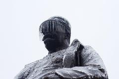 Estatua negra del soldado con los carámbanos que cuelgan de su sombrero imagen de archivo