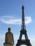 Estatua que mira en la torre Eiffel Imagenes de archivo