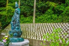 Estatua que representa a una diosa budista que vigila sobre muchas estatuas más pequeñas de Bhuddist Munakata, Japón foto de archivo