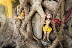 Estatua quebrada de Buda y muñecas religiosas viejas debajo del árbol en Thail Imágenes de archivo libres de regalías