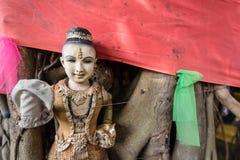 Estatua quebrada de Buda y muñecas religiosas viejas debajo del árbol en Thail Fotos de archivo