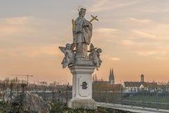Estatua santa en Regensburg con la bóveda San Pedro en el fondo durante puesta del sol Fotos de archivo libres de regalías