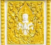 Estatua sobre la religión en la pared, templo tailandés Foto de archivo libre de regalías
