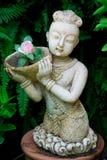 Estatua tailandesa del niño en un jardín Fotografía de archivo